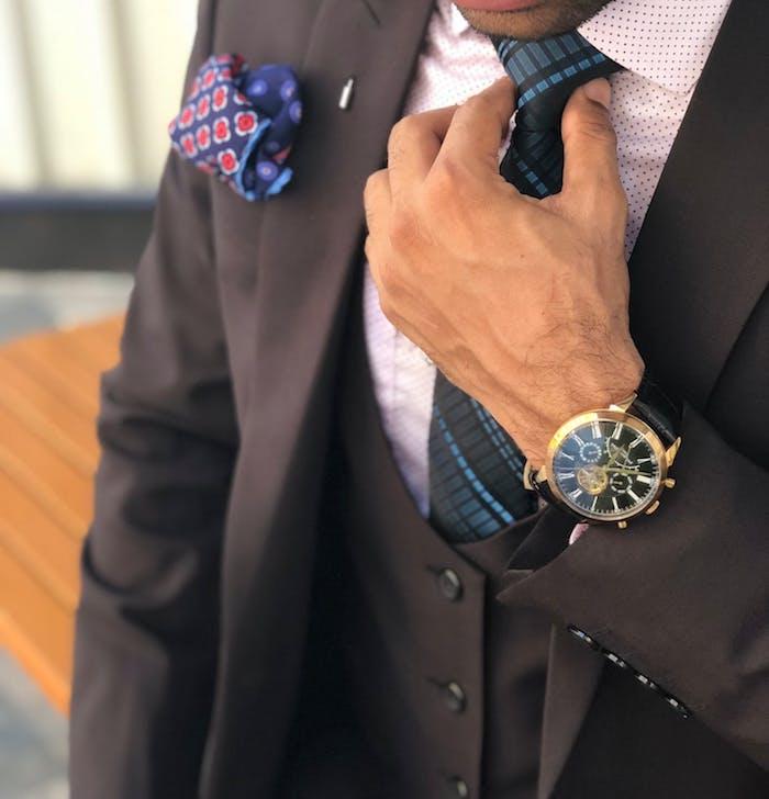 Schwarzer Herrenanzug, weißes Hemd und blaue Krawatte, Armbanduhr mit schwarzem Lederriemen