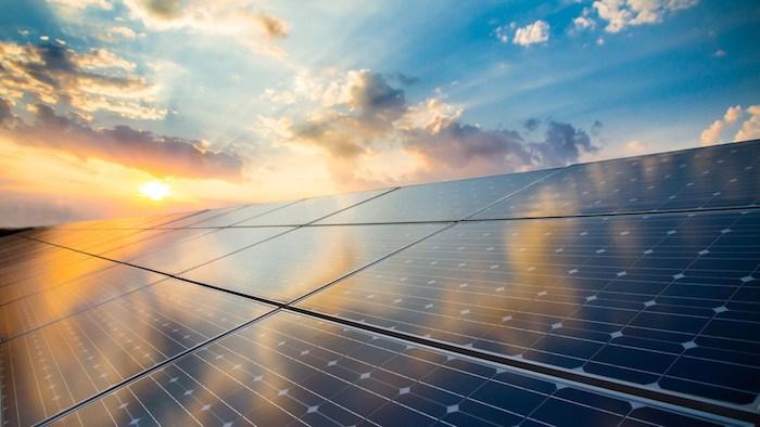 viele Photovoltaikanlagen und ein sonnenuntergang