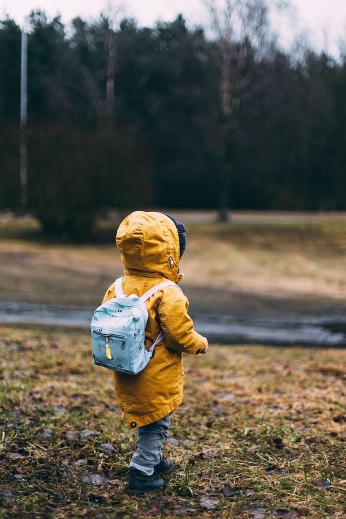 Süßes Kind mit gelber Regenjacke und blauem Rucksack