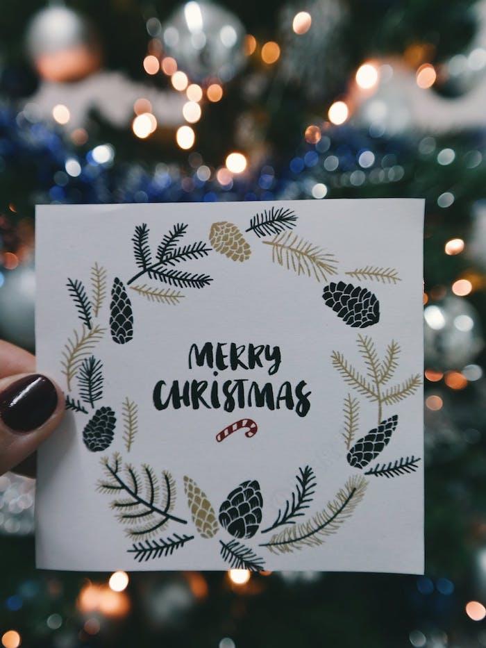 Weihnachtskarte mit Kranz aus Tannenzweigen und Tannenzapfen, Frohe Weihnachten