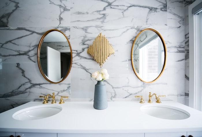 Runde Badezimmerspiegel, Marmorfliesen und weißer Waschbecken, weiße Rosen in kleiner Vase