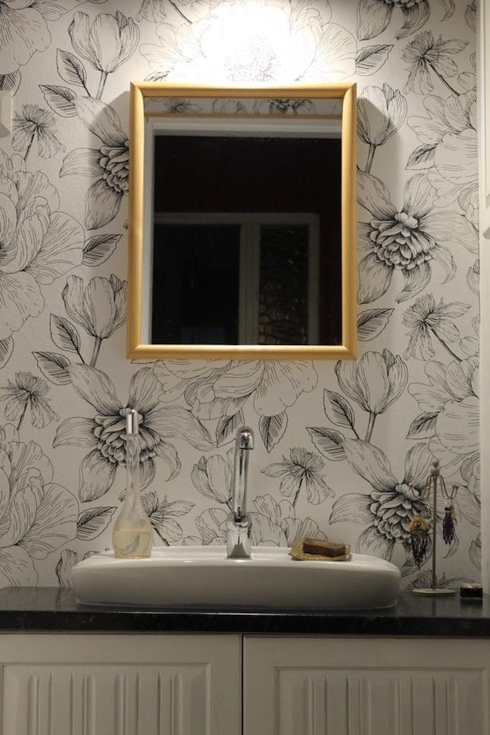 Viereckiger Badspiegel mit goldenem Rahmen, weiße Tapete mit Blumenmuster