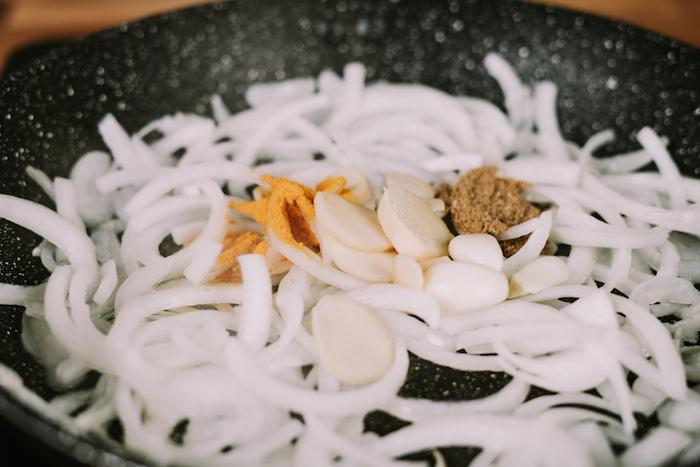 cremesuppen rezepte, kürbissuppe zubereitung, geshcnittene zwiebel mit knobluach uns gewürz