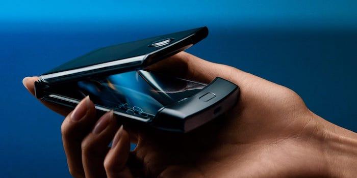 eine hand einer jungen frau mit einem kleinen schwarzen smartphone, das neue motorola razr mit einem faltbaren bildschirm