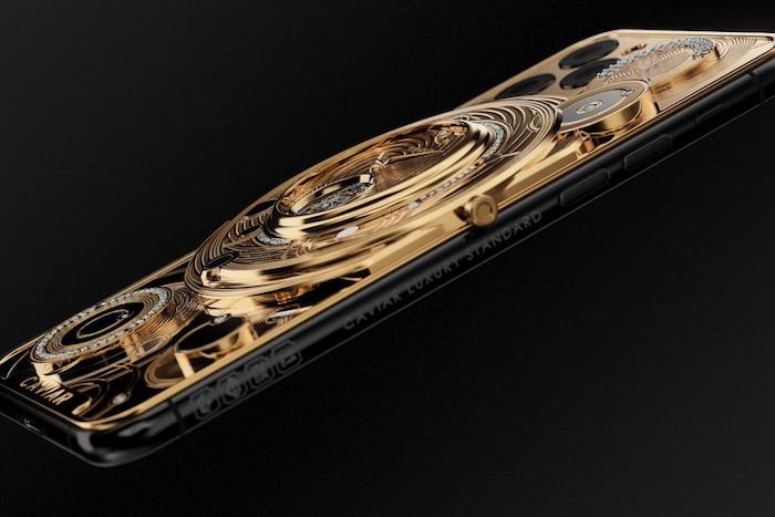 ein goldenes handy, ein iphone 11 pro mit kamera und veiner uhr us gold und vielen kleinen diamanten, handy von caviar