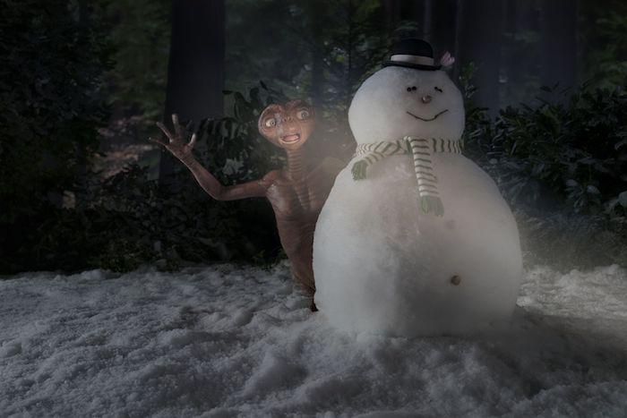 ein weißer schneemann mit einem schal im garten, ein außerirdischer im garten, außerirdischer mit blauen augen