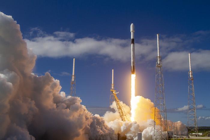 das projekt starlink von elon musk, ein blauer himmel mit wolken und eine große weiße rakete und feuer