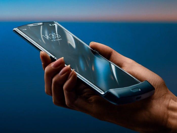 hand einer frau mit einem schwarzen smartphone mit einem faltbaren bildschirm, das neue motorola razr