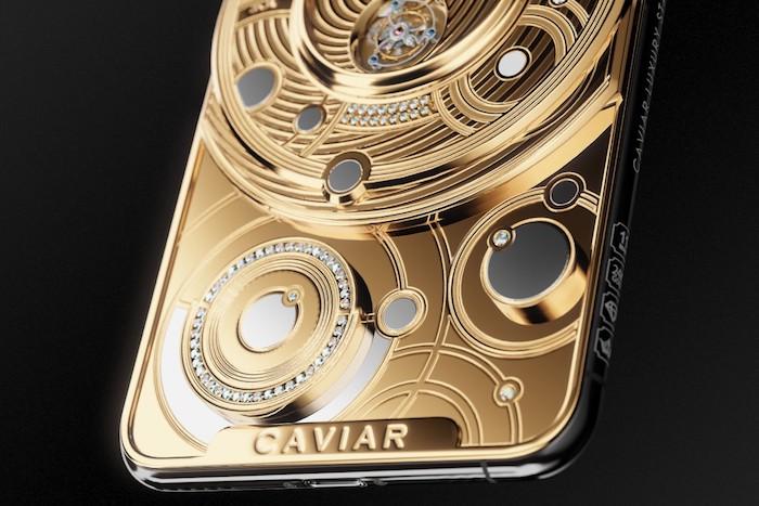 ein goldenes smartphone von dem hersteller caviar, ein iphone 11 pro mit einer uhr aus gold und diamanten