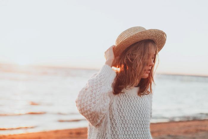 Offene mittellange Haare, weißes Pullover und Sommerhut