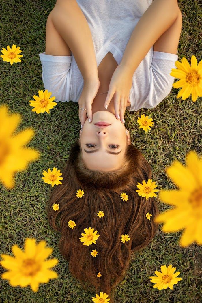 Lange braune offene Haare, weißes T-Shirt, gelbe Blumen