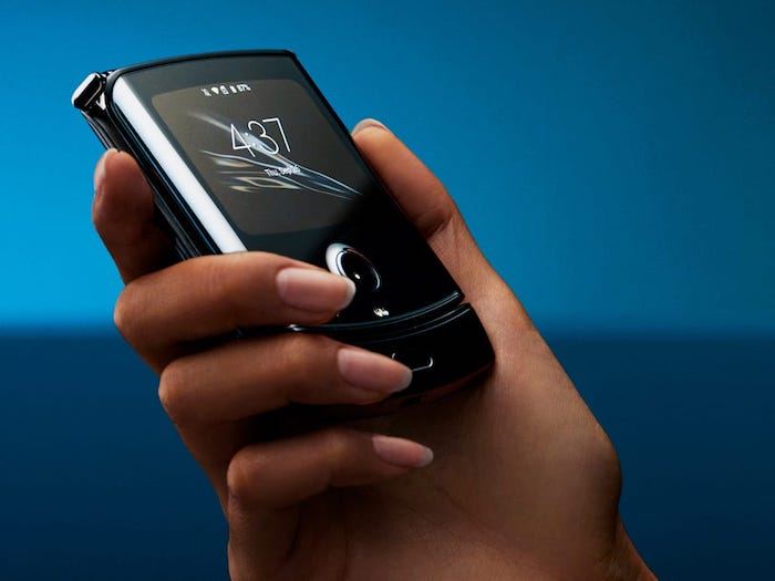 kleines schwarzes smartphone mit einem kleinen . display auf der rückseite, eine hand einer frau, das neue faltbare motorola razr