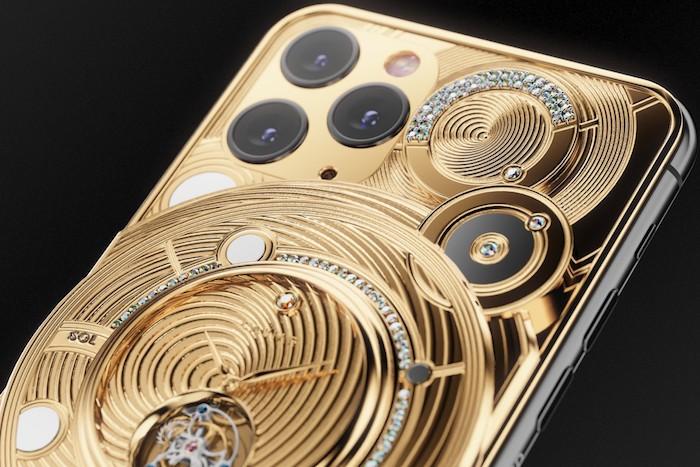 eine uhr aus vielen kleinen goldenen teilen, das handy iphone 11 pro mit drei kameras, ein luxus smartphone