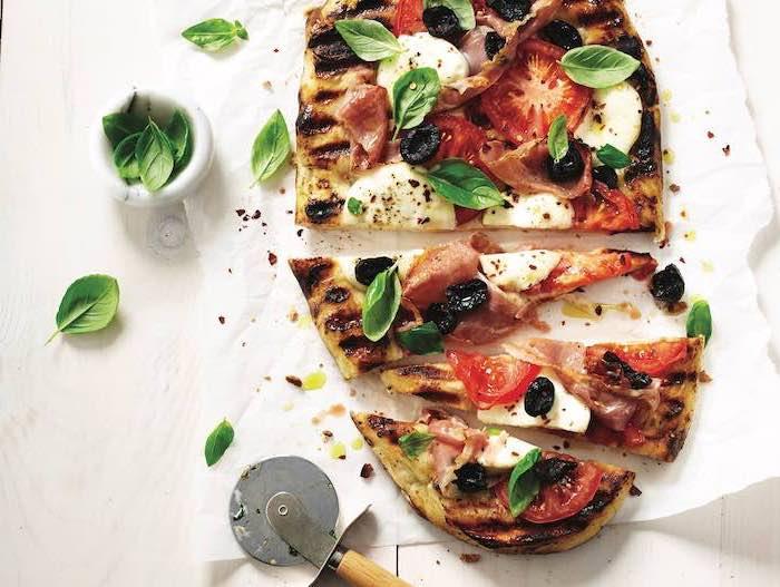 schnelle einfache gerichte, pizza mit tomaten, mozzarela, fleisch und frischem basilikum