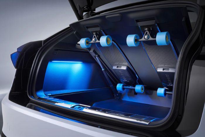 zwei schwarze elektro longboards und ein weißes auto, das neue volkswagen id space vizzion, das erste elektropassat