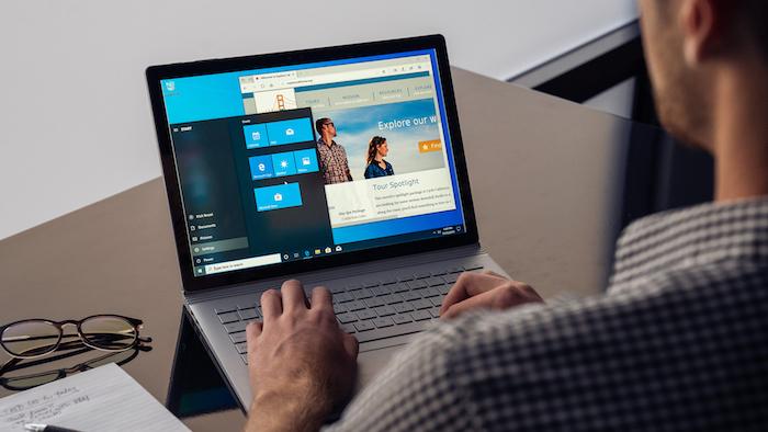 ein mann mit hemd, ein laptop mit dem betriebssystem windows 10 und brille, das neue update für windows 10