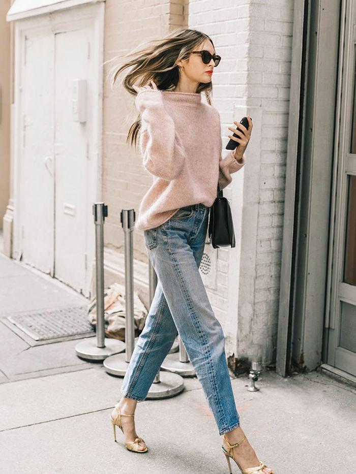 Dame in Jeans und goldene Sandalen, pinker Pullover und kleine, schwarze Tasche