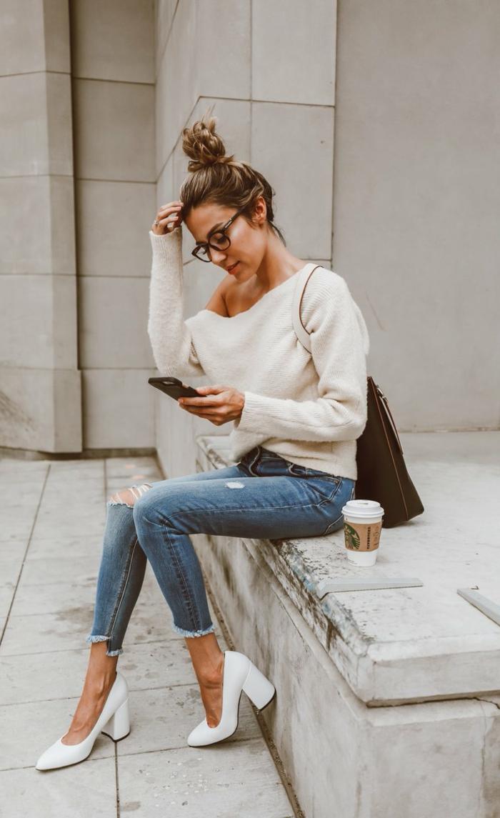 Frau mit hochgesteckten Haaren, Jeans und Pulli mit weißen Pumps