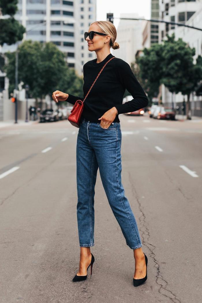 Dame in Jeans, schwarze High Heels, rote Tasche aus Leder und schwarze Bluse, sportlich elegante outfits damen