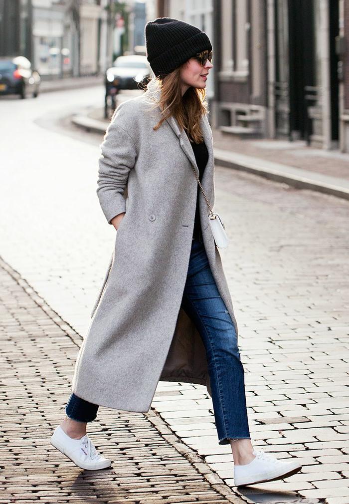 Dame im grauen Mantel, gepaart mit Jeans, weiße Sneakers und schwarze Mütze