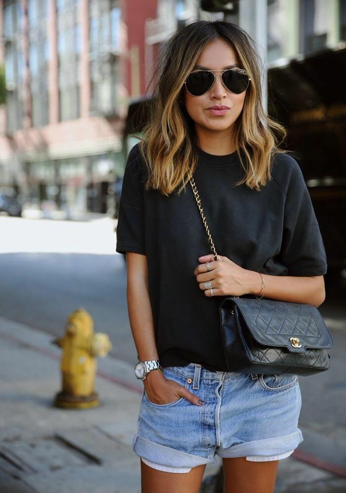 Dame im Sommeoutfit, mit Jean Shorts, basic T-Shirt und Handtasche aus Leder, kleiderordnung casual