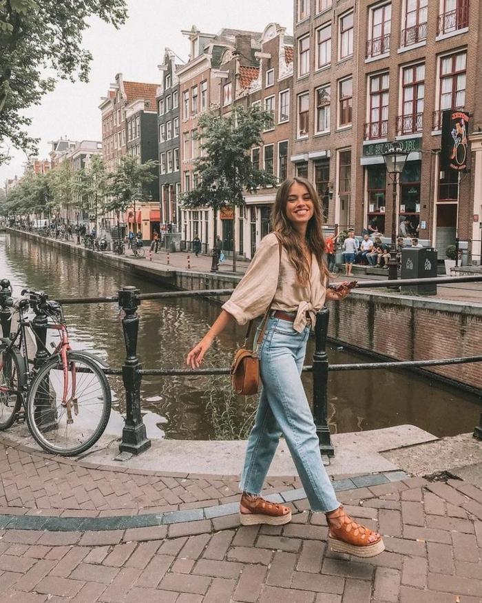 Dame im casual outfit mit lässige Jeans, weite Bluse und brauner Tasche, dresscode sportlich elegant