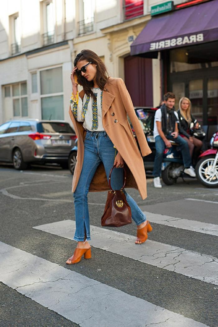 Schick angezogene Dame mit hellem Mantel, Jeans und gemusterter Bluse, dresscode leger