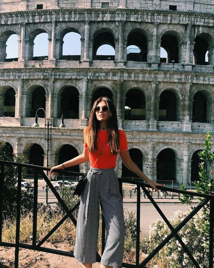 Leger angezogene Dame in weiten Hosen, orangenes Oberteil und schwarze Tasche aus Leder, dresscode sportlich elegant