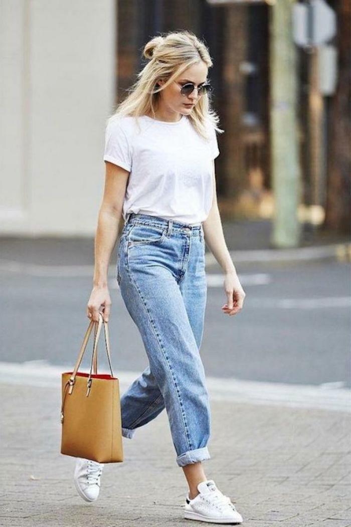 Blonde Frau in Mom-Jeans, weißes T-Shirt und weiße Sneakers, mit brauner Handtasche