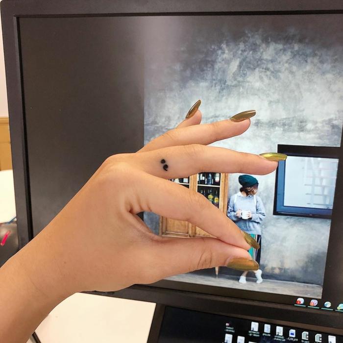 Kleines semicolon tattoo am Mittelfinger, was bedeutet ein semikolon, Hand mit goldenem Nagellack