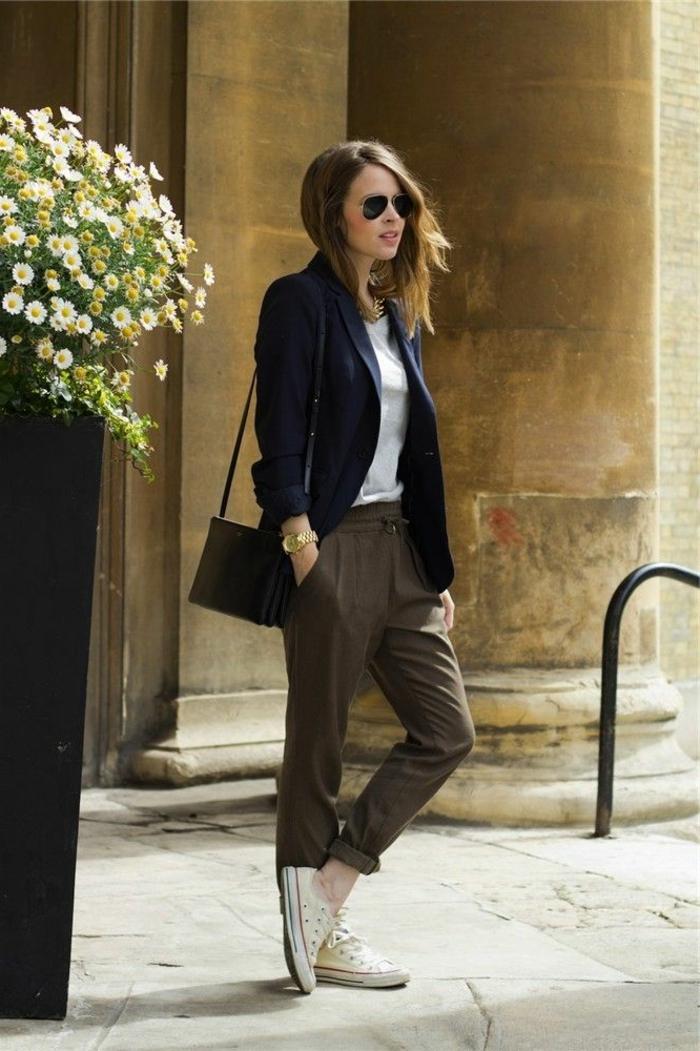 Frau im schwarzen Blazer, dunkle Hosen, weiße Sneakers und kleine Handtasche