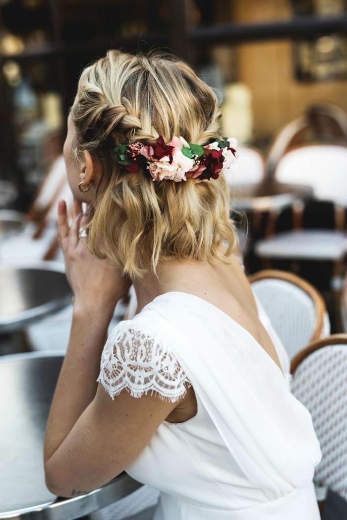 Blumenkranz mit weißen und roten Rosen im Haar einer blonden Frau, frisuren für kurze haare, geflochtene halb hoch halb runter Frisur, Frau im weißen Kleid sitzend, Kurzhaarfrisuren Damen