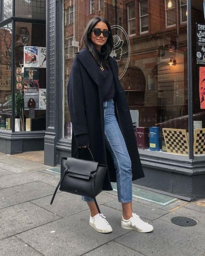 Casual angezogene Frau, mit dunklem Mantel, helle Jeans, weiße Sneakers