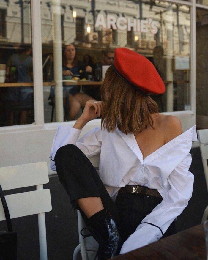 frauen kurzhaarfrisuren, braune Haare, Frau im roten Barett, weiße oversized Bluse und schwarze Jeans,