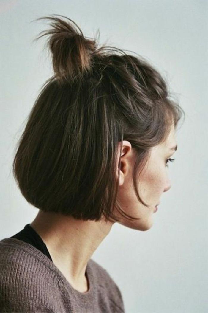 messy halb haarknoten, frau mit dunkelbraunen haaren, frisuren frauen kurz, brauner pullover