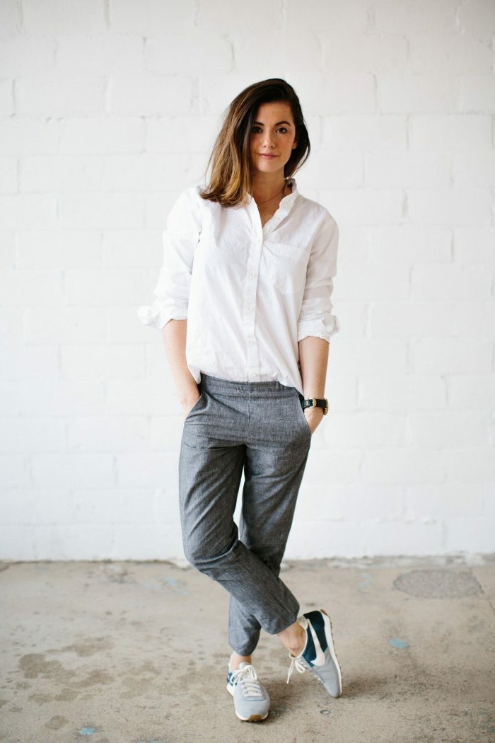 Dame mit dunkelbraunen Haaren, weite Hosen, weißes Hemd und Sneakers