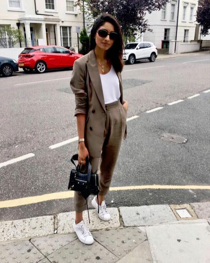 Lässig und stylish angezogene Frau im modernen Anzug, mit weißen Sneakers und Oberteil