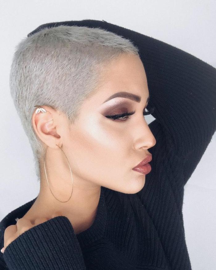 blonder Buzz cut Haarschnitt, modische Kurzhaarfrisuren, geschminktes Gesicht mit Highlighter, große Creolen und Schmetterling Ohrring