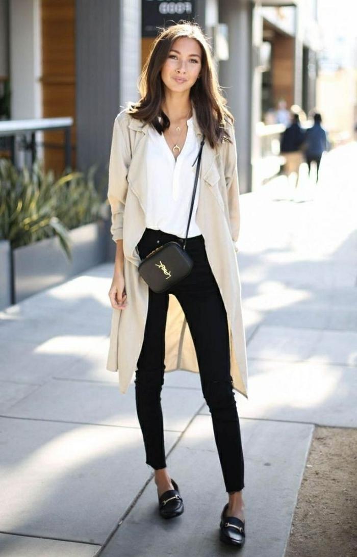 Dame im hellen Cardigan, schwarze skinny Jeans, Bluse und klassische Schuhe