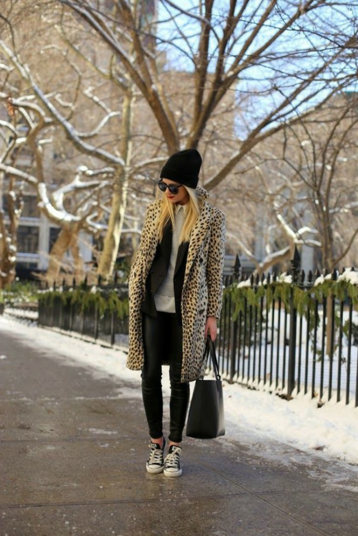 Frau im Mantel mit Leopardenmuster, schwarze Hosen, graue Bluse und schwarze Mütze