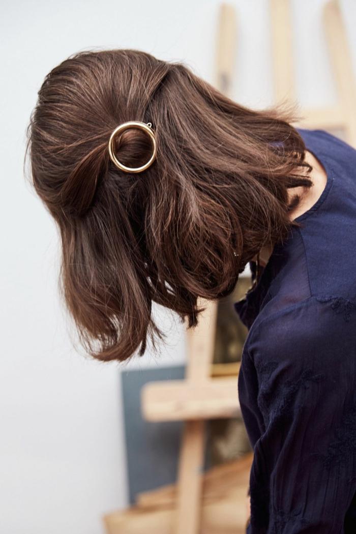 frisuren frauen kurz, braune Haare befestigt mit einer goldenen Haarnadel, Frau in blauer Bluse