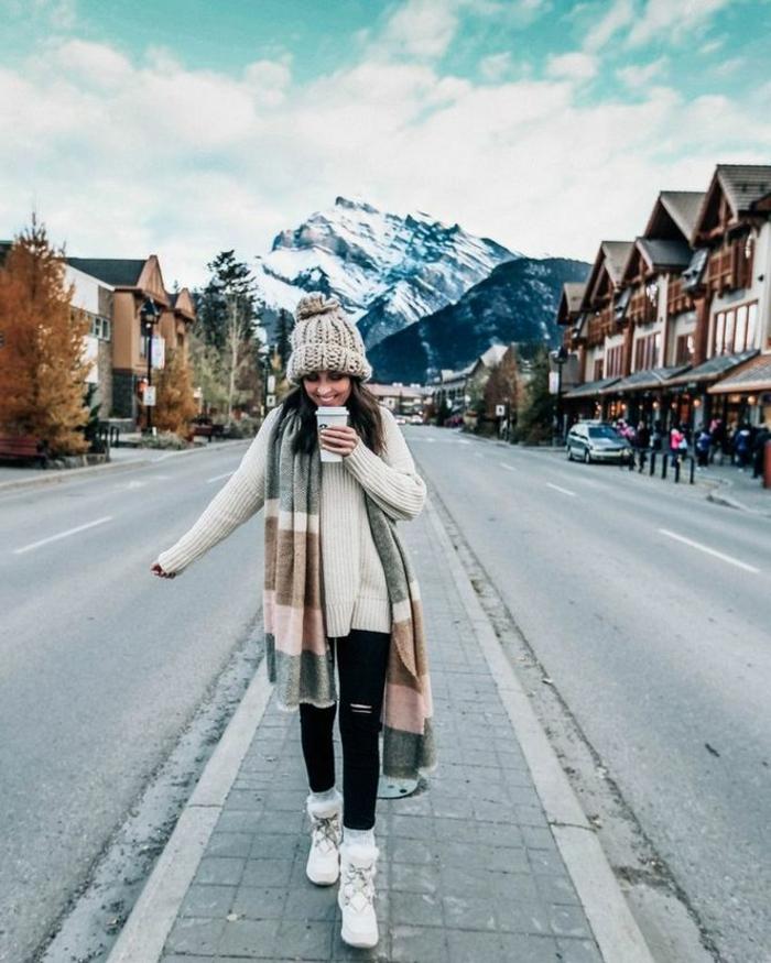 Dame im Winter Outfit mit schwarzen Jean, Winterstiefel, dicker Schal, dicke Mütze und cozy Pulli,smart casual dresscode für damen