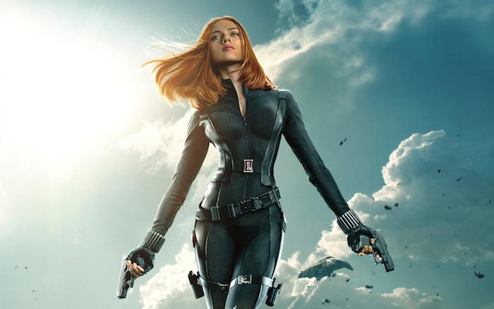 der film black widow mit der schauspielerin scarlett johansson, eine frau mit zwei pistolen und mit einem schwarzen kostüm