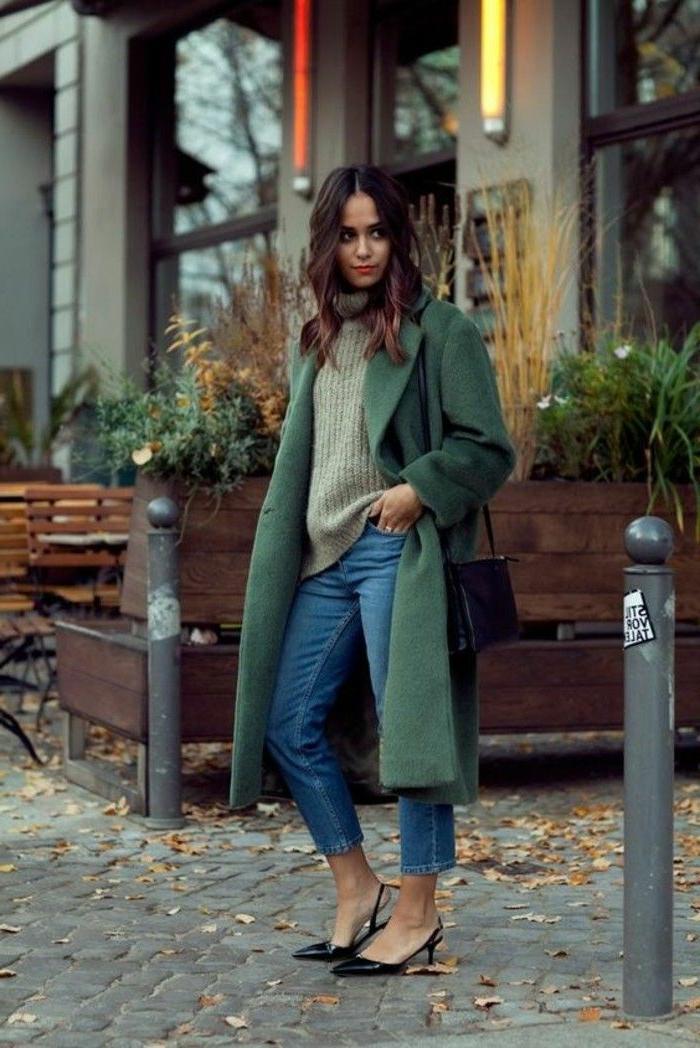 Dame im grünen Mantel mit Jeans, Rollkragenpullover und schwarze Heels