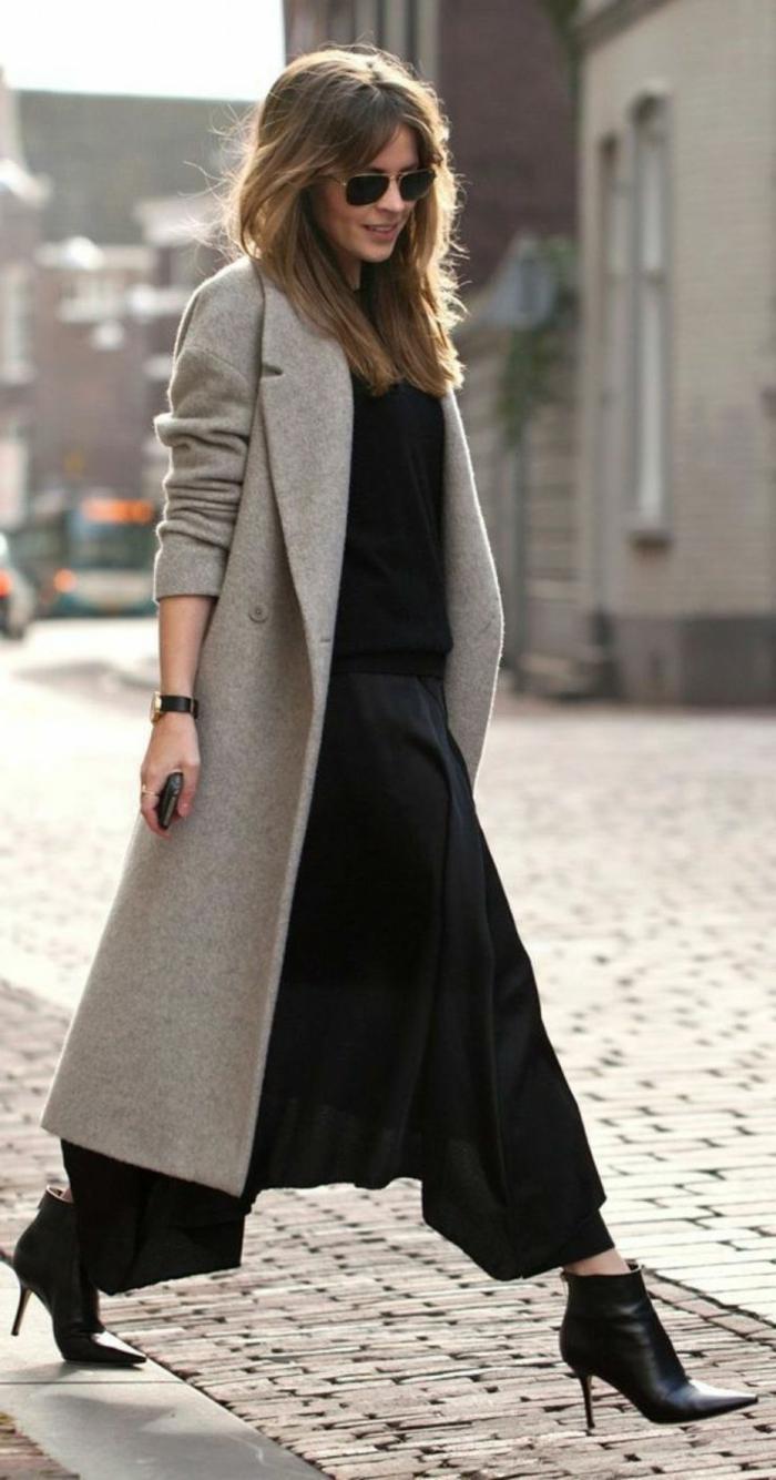 Dame in weiten Hosen, schwarze Stiefeln aus Leder und schwarze Bluse