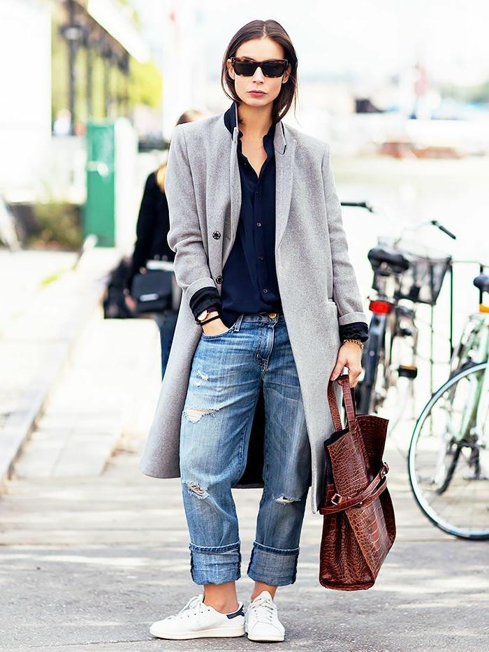 Lässig angezogene Frau in Boyfrien Jeans, mit grauem Mantel, dunkler Bluse