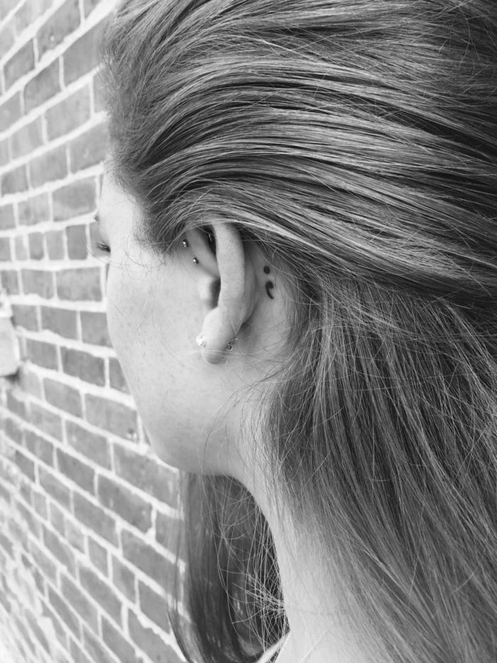 Semicolon Tattoo hinter dem Ohr einer Frau mit Piercing, dunkelblonde Haare, project semicolon,