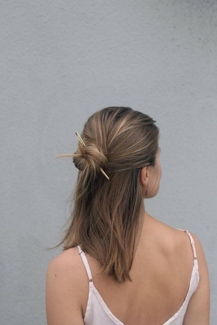 Frau mit dunkelblonden Haaren, Halb hoch halb runter mir Haarknoten, befestigt mit einer Nadel, weißes Top