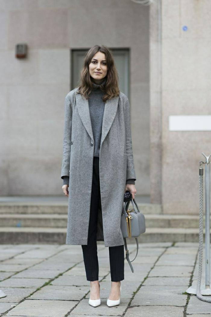 Dame im eleganten Outfit mit langem Mantel, schwarzer Hose, Pulli und kleiner Tasche