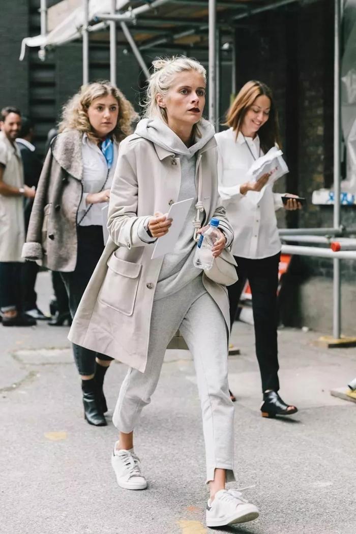 Frau im monochromen Outfit, stilvoller Mantel, oversized Kapuzenpullover und weiße Sneakers, sportlich elegante outfits damen